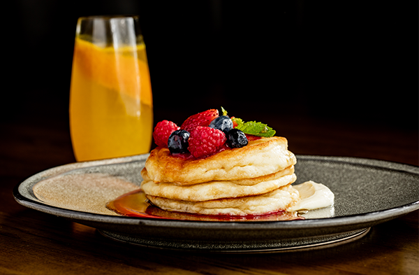 Breakfast pancakes with fruit on top and orange drink